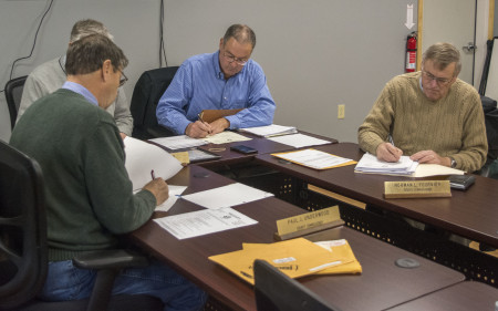 County Commissioners discuss inevitable wage increases in the Sheriff's Department during their Nov. 16, 2016 meeting in Caribou's Emergency Management Agency building. From left, around the table, Presque Isle Commissioner Paul Underwood, Houlton Commissioner Paul Adams, County Administrator Douglas Beaulieu, and Wallagrass Commissioner Norman Fournier. Christopher Bouchard | Aroostook Republican)