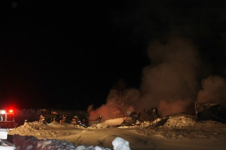 Firefighters contain a fire at a metal barn on Blaine School Road in Fort Kent on Sunday night, Jan. 1, 2017. (Jessica Potila | SJVT / FhF)