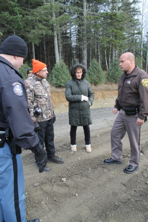 John Ezzy, left, and his wife Anne, talk with a Maine State Police trooper and Aroostook County Sheriff's Department deputy Monday, Oct. 31, following an incident on Pelletier Avenue, in which an abutting landowner plowed up a section of disputed road and allegedly assaulted a passerby. (Don Eno | SJVT/FhF)