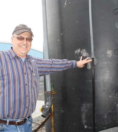 Madawaska Public Works Director Yves Lizotte points out the level of molasses in an outdoor tank, Thursday, March 1, at the department's garage. Public Works is trying a new system that uses molasses to help its sand/salt mixture adhere better to winter roads. (Don Eno | SJVT/FhF)