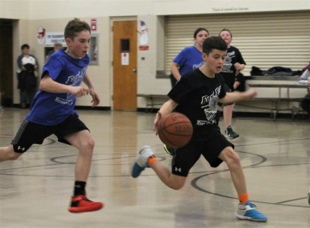 Fort Kent Magic player Keegan Cyr is hot on the heels of the Spurs' Pierson Caron in search of a steal at a Parks and Recreation Department Round Robin tournament on Thursday, March 9. (Jessica Potila | SJVT/FhF)